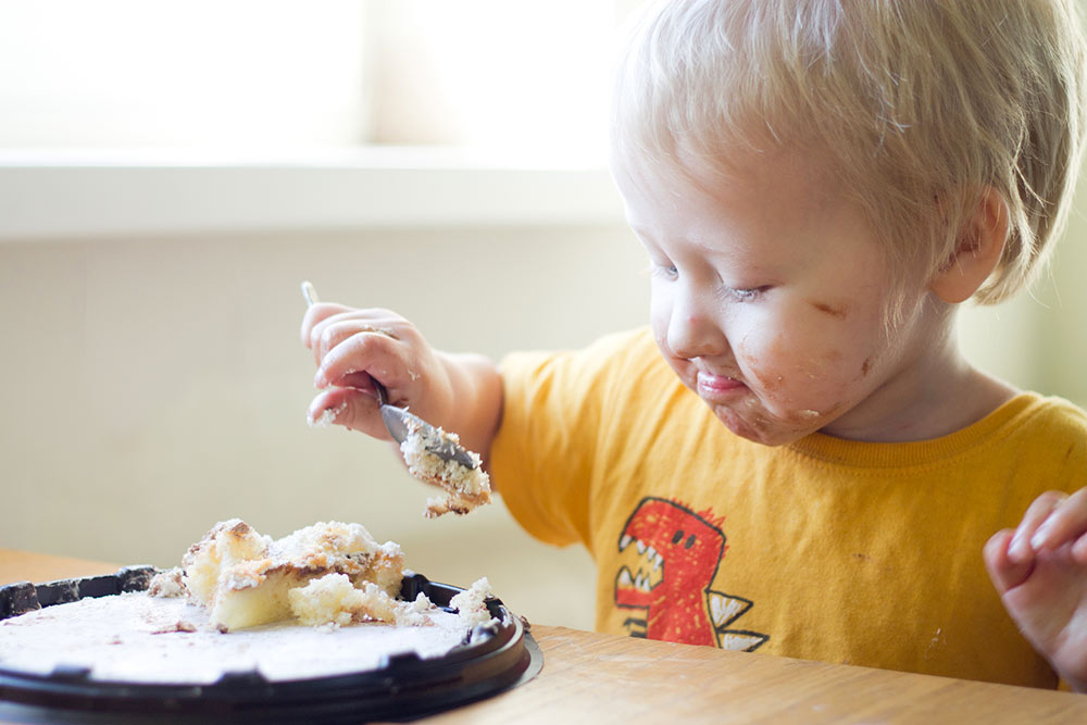 little kid messily eating cake